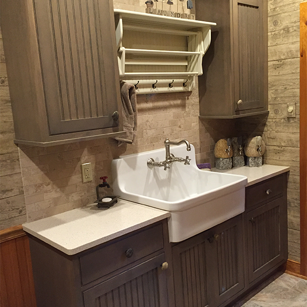 Cabinets above and below farm utility sink provide ample storage.